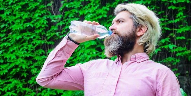 Mann trinkt wasser. gesunder lebensstil. durstige männliche trinkflasche wasser. trinkkonzept.