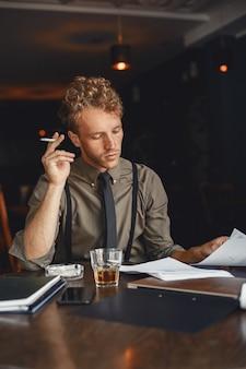 Mann trinkt whisky. geschäftsmann liest dokumente. regisseur in hemd und hosenträgern.