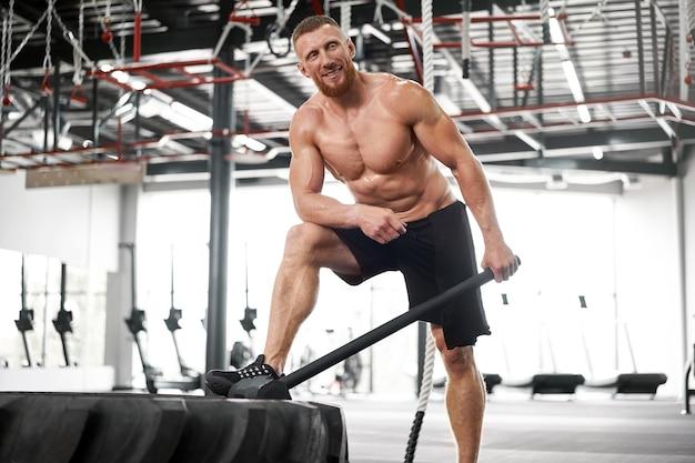 Mann turnhalle hammerschlag traktorrad schlägt riesigen reifen athlet sportlicher mann mittlerer erwachsener gutaussehender sportler bodybuilder gewichtheber idealer körper