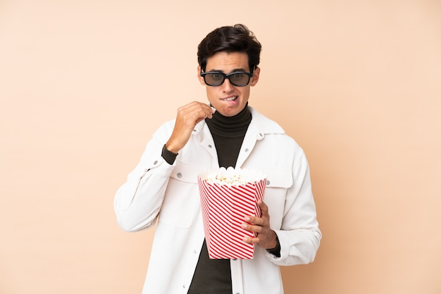 Mann über wand mit gläsern 3d und halten eines großen eimers popcorns