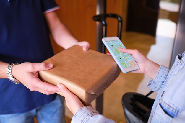 Mann übergibt einem zusteller auf dem telefonbildschirm ein paket, der versandweg wird auf einer karte angezeigt