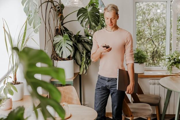 Mann überprüft das telefon, geschäftsmann mit laptop im arbeitsbereich im öko-café mit pflanzen