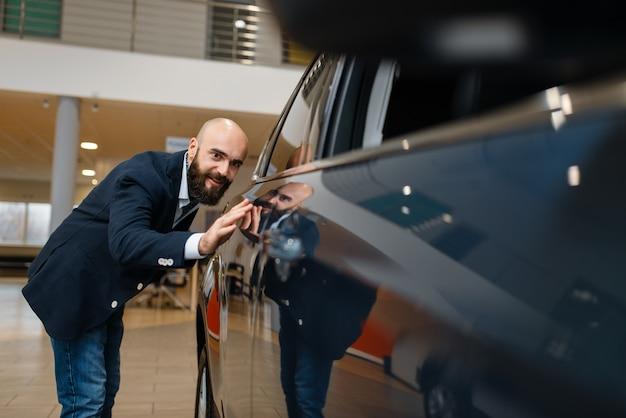 Mann überprüft die lackierung des neuen automobils im autohaus. kunde im fahrzeugausstellungsraum, männliche person, die transport kauft, autohändlergeschäft
