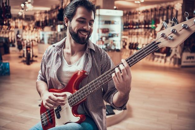Mann überprüft e-gitarre, bevor er im musikgeschäft kauft