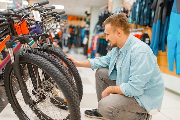 Mann überprüft fahrradreifen, einkaufen im sportgeschäft. extremer lebensstil der sommersaison, aktives freizeitgeschäft, kunden, die fahrradausrüstung kaufen