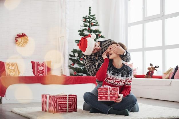 Mann überraschen seine frau zu weihnachten im schönen zimmer mit weihnachtsschmuck