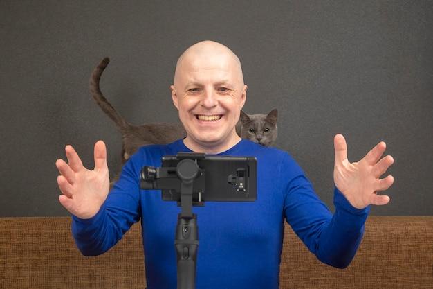 Mann überträgt ein heimvideo auf ein smartphone mit stabilisator