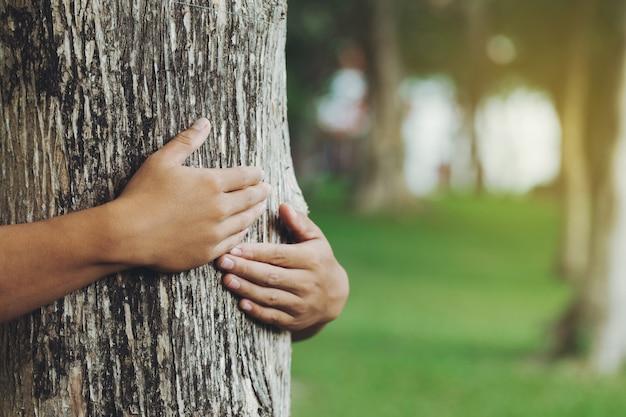 Mann umarmt einen grünen baum im waldnatur und öko-lifestyleworlds-tag