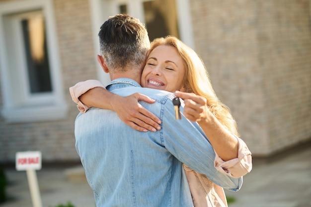 Mann umarmt glückliche frau mit schlüsseln