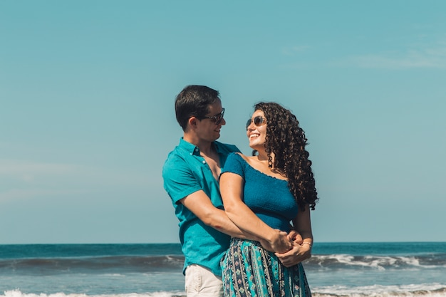 Mann umarmt lächelnde frau am strand