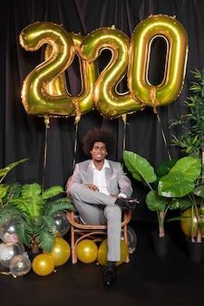 Mann umgeben durch goldene ballone des guten rutsch ins neue jahr 2020