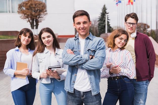 Mann umgeben von intelligenten studenten mit den büchern, die kamera betrachten