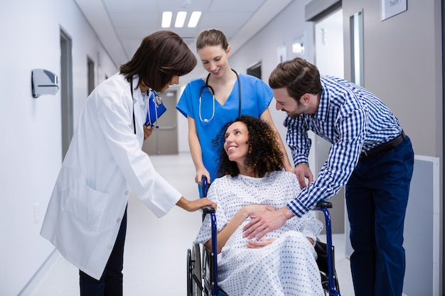 Mann und ärzte trösten schwangere frau im korridor