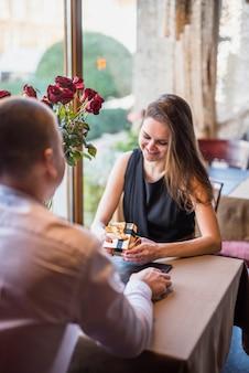 Mann und attraktive lächelnde frau mit präsentkarton bei tisch