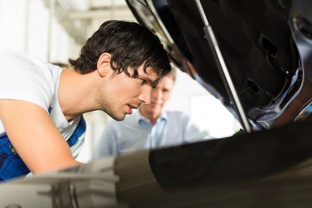 Mann und automechaniker, die unter einer haube schauen
