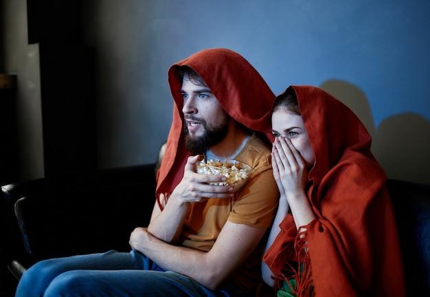 Mann und eine frau sitzen auf sofa vor dem fernseher drinnen