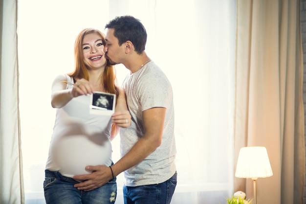 Mann und eine schwangere junge frau warten zu hause am fenster auf ein kind. liebevolle familie, mann und frau. ultraschallfoto des embryos in den händen halten