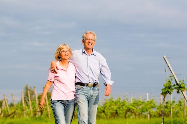 Mann und frau, älteres paar, spazieren im sommer oder draußen im weinberg
