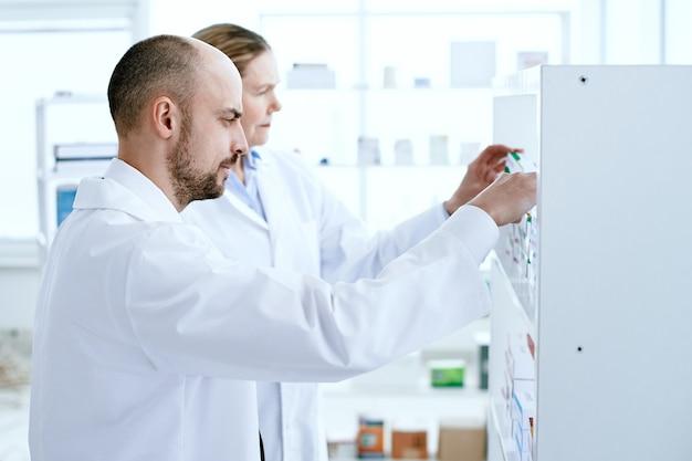 Mann und frau apotheker diskutieren medikamente