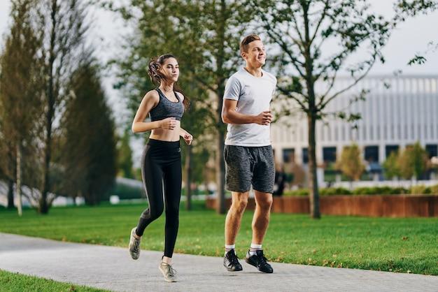 Mann und frau athleten, die in der natur im park joggen.
