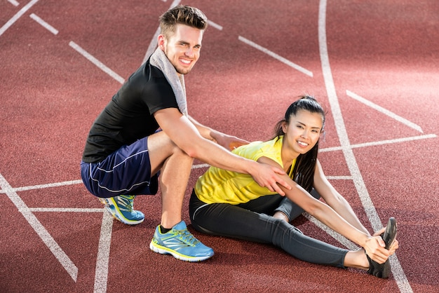 Mann und frau auf aschenbahn der sportarena, die übungen ausdehnt