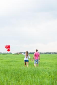 Mann und frau auf dem feld mit roten luftballons. glückliches paar auf naturrückansicht
