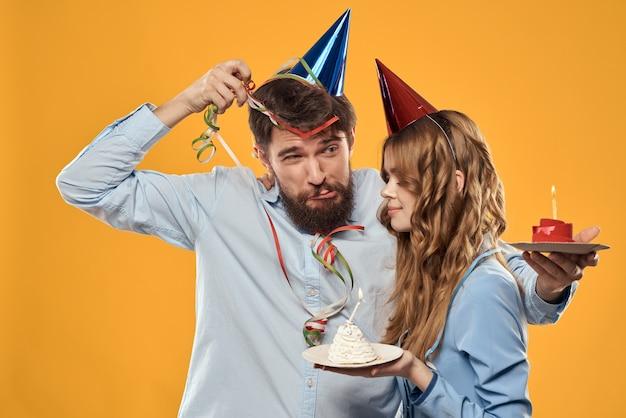 Mann und frau auf einer party in mützen und mit lametta kuchen spaß gelbe wand