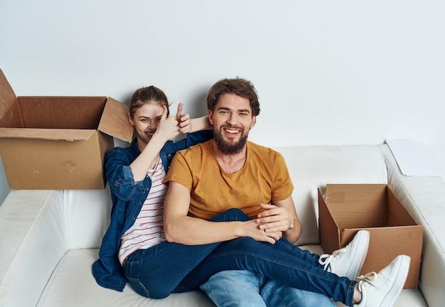 Mann und frau auf weißem sofa-innenkarton-lebensstil. hochwertiges foto