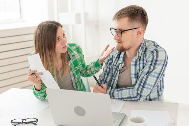 Mann und frau besprechen den scheckbetrag für die zahlung der wohnung und vergleichen ihn mit den preisen auf der offiziellen website, während sie mit dem laptop am tisch sitzen. konzept der zahlung von stromrechnungen.