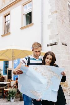 Mann und frau betrachten die karte, die in der alten stadt steht