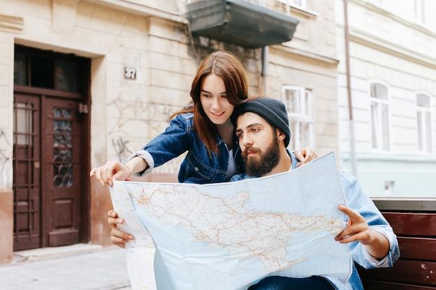 Mann und frau betrachten die karte, die irgendwo auf der bank in einer alten stadt sitzt
