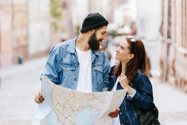Mann und frau betrachten die karte, die irgendwo in einer alten stadt steht