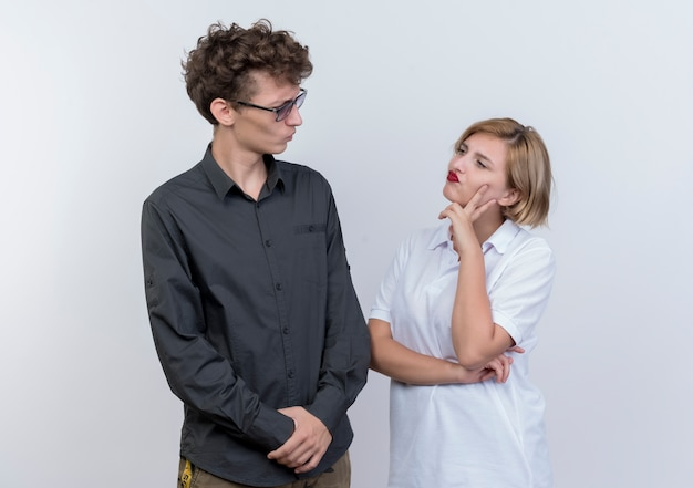 Mann und frau des jungen paares, die einander mit skeptischem ausdruck betrachten, der über weißer wand steht