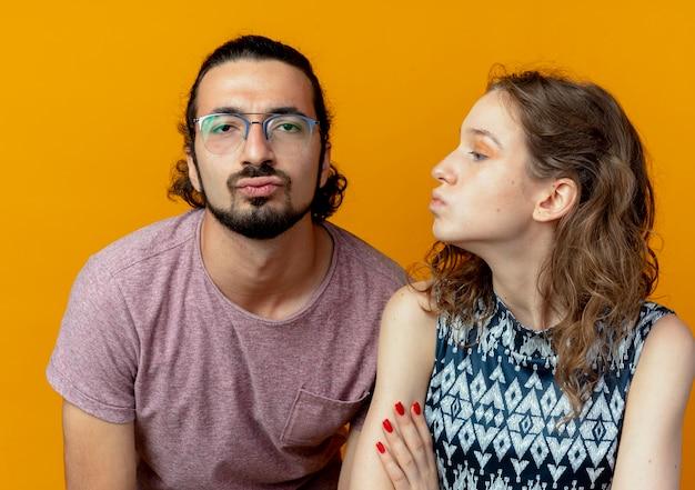 Mann und frau des jungen paares, die einen kuss über orange wand blasen