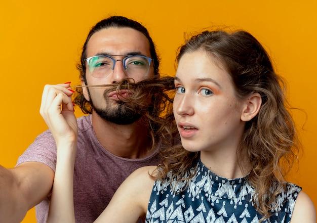 Mann und frau des jungen paares imitieren schnurrbart mit den haaren ihrer freundin über orange wand