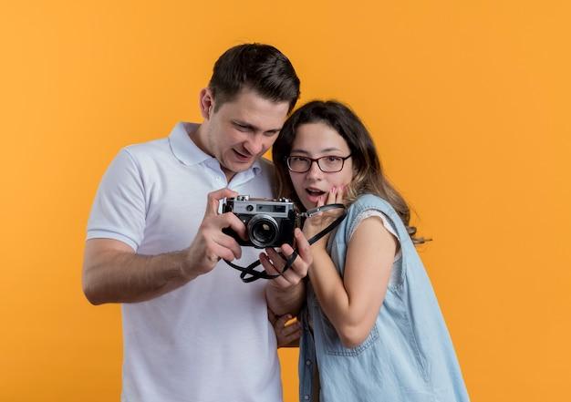 Mann und frau des jungen paares in der freizeitkleidung, die fotokamera überrascht und glücklich über orange betrachtet