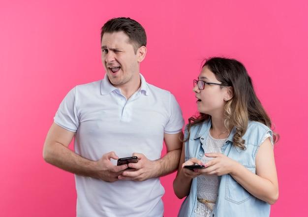 Mann und frau des jungen paares in der freizeitkleidung, die smartphone-mann zwinkert und lächelt, während seine freundin ihn verwirrt betrachtet, der über rosa wand steht