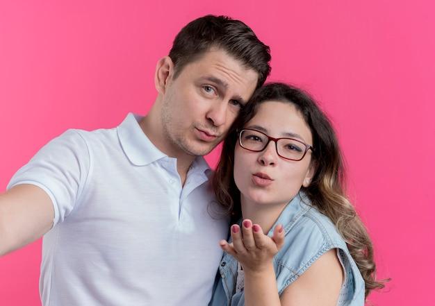 Mann und frau des jungen paares in der freizeitkleidung, die zusammen glücklich in der liebesfrau steht, die einen kuss mit der hand vor ihr über rosa wand bläst