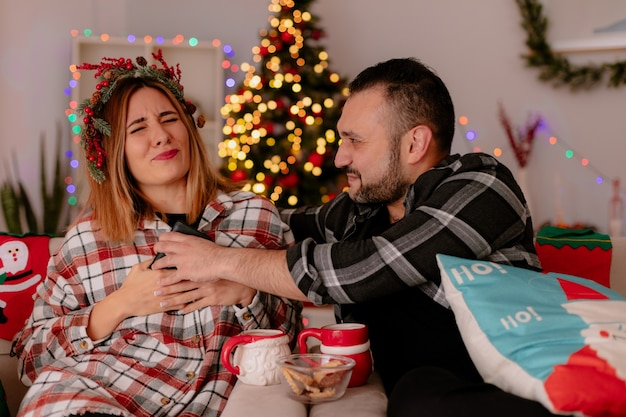Mann und frau des jungen paares mit smartphone, das auf einer couch mit tassen des teestreit-dekorierten zimmers mit weihnachtsbaum im hintergrund sitzt