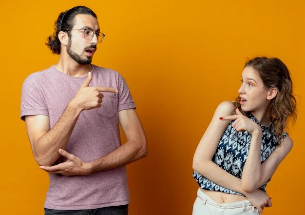 Mann und frau des jungen paares zeigen aufeinander und beschuldigen sich gegenseitig über der orangefarbenen wand