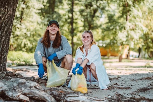 Mann und frau, die abfall vom park aufheben. sie sammeln den müll im müllsack