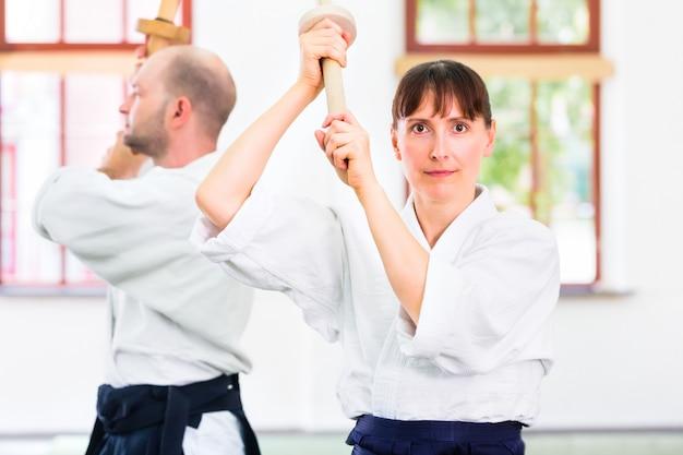 Mann und frau, die aikidoschwertkampf haben