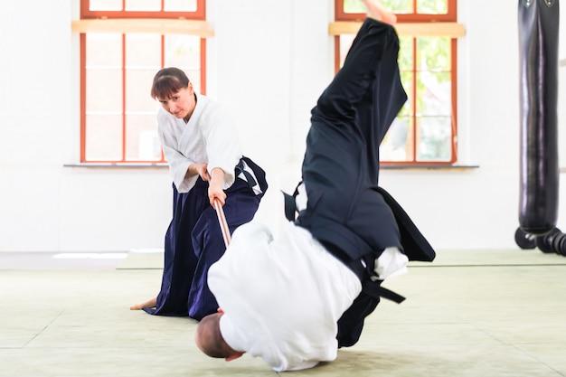 Mann und frau, die aikidostockkampf haben