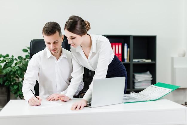 Mann und frau, die an dem geschäft im büro arbeiten