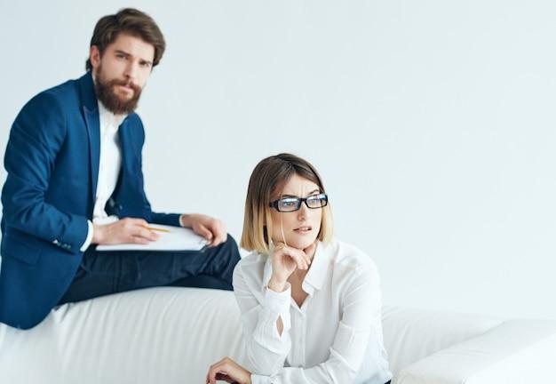 Mann und frau, die auf dem couchkommunikationsarbeitsprofiteam sitzen