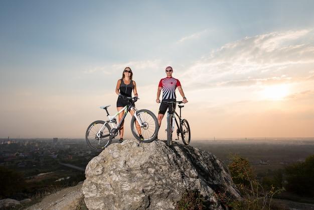 Mann und frau, die auf einem felsen mit ihren fahrrädern unter abendhimmel bei sonnenuntergang stehen