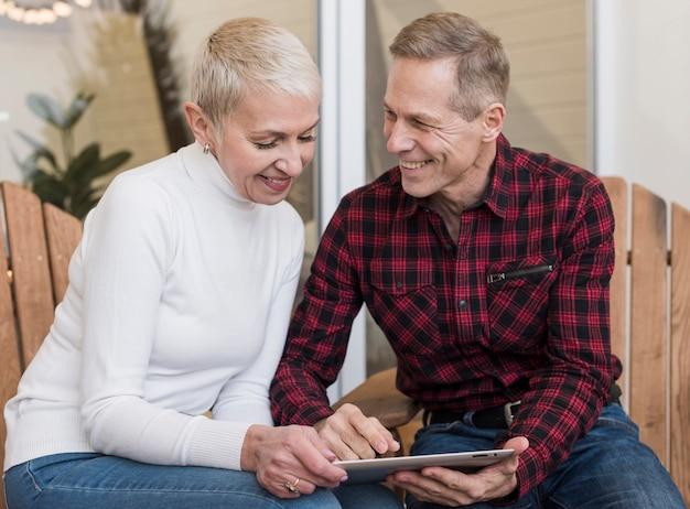 Mann und frau, die auf ihrer tablette schauen