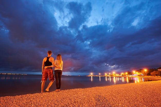 Mann und frau, die auf pebble beach an der dämmerung auf drastischem blauem hintergrund des bewölkten himmels des ruhigen wassers stillstehen
