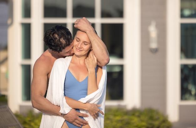 Mann und frau, die auf unendlichem pooldeck in badeanzügen entspannen
