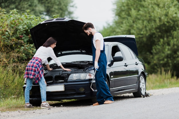 Mann und frau, die automotor überprüfen